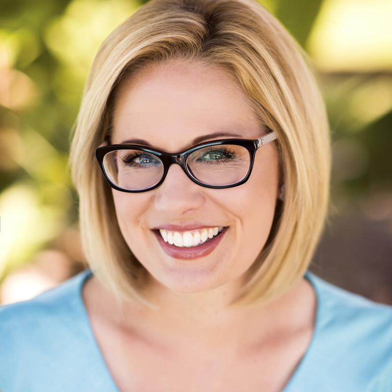 Kyrsten Sinema headshot in front of trees.