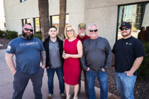 Kyrsten Sinema standing with a group of six veterans.